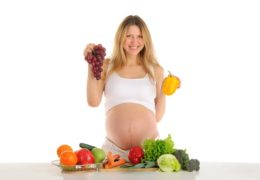 Happy pregnant woman with fruits and vegetables